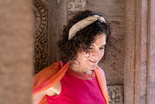 Image of woman in India, with short curly brown hair, wearing skinny, beige colored, khadi, wire-framed headband with traditional clothing in pink, orange, and gold.