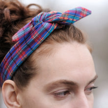 Photo of woman with red hair wearing colorful plaid bandana tied in a bow.