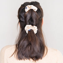 Two Jute large beige silk scrunchie with white piping in a double pony tail.