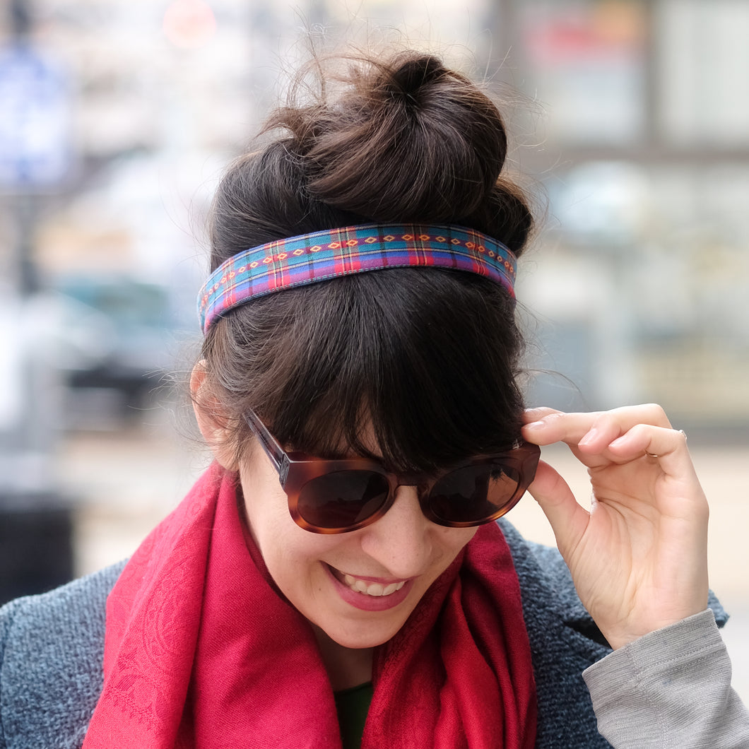 Woman with dark hair and bangs wearing her hair in a bun and a blue, teal, pink, and yellow woven plaid headband.