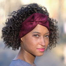 Woman with natural curly dark hair wearing burgundy vegan suede head wrap with knot at center in front of a blurred background. Berry/ merlot/ wine/ maroon faux suede knit wire framed headband. Sculptural, comfortable, wide hair scarf.  90s, 80s, 70s, 60s, 50s, pin up, punk rock, hippie, afro punk, bohemian, vintage, classic, glamorous, stylish, solid colored, saturated color hair accessory.