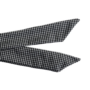 Overview of the ends of a black and white gingham wire-framed bandana tied in a bow.
