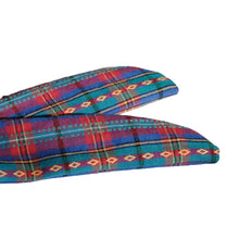 Overview of the tapered ends of a blue, teal, pink, and yellow woven plaid headband on white background.