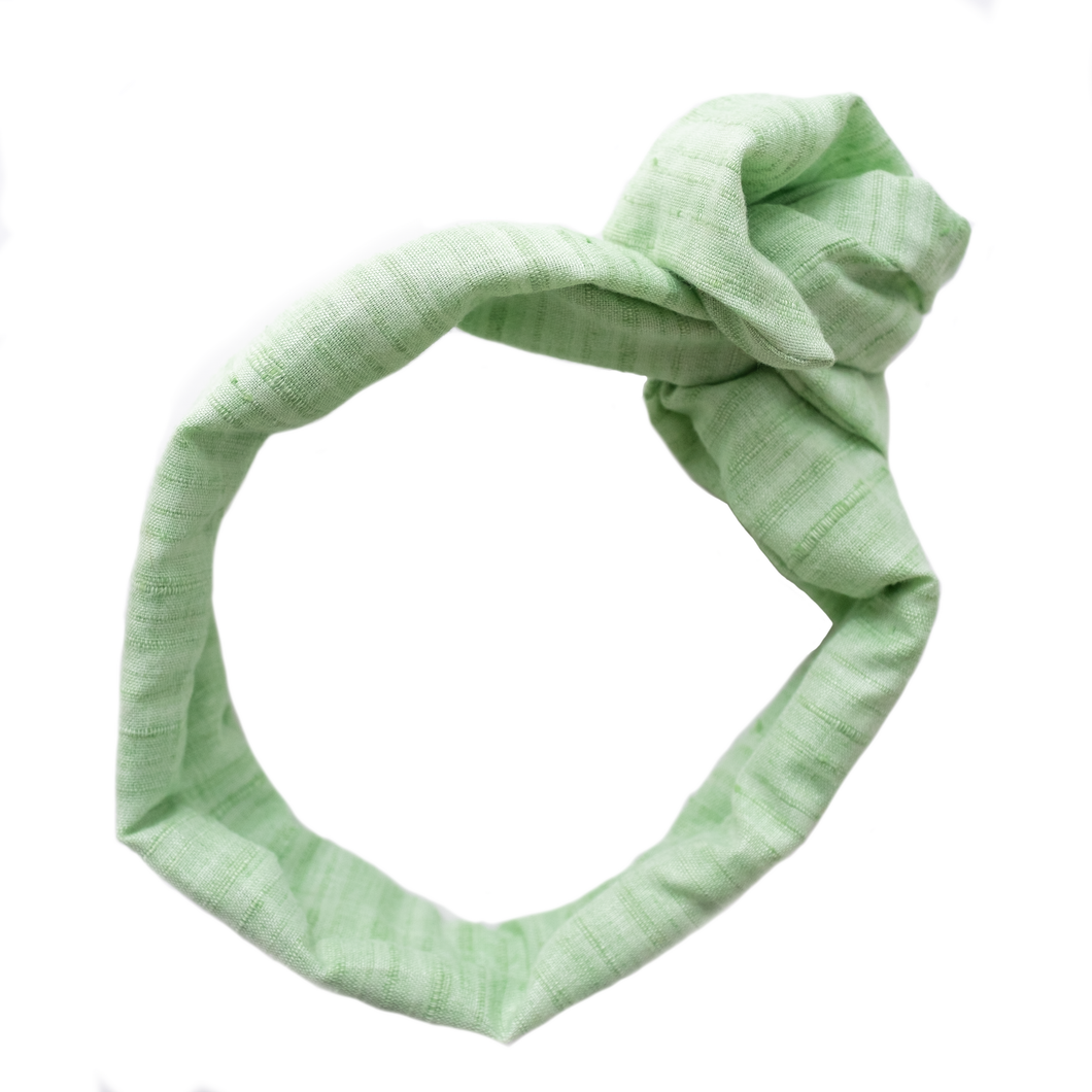 Overview of a pale mint green, wire-framed, scarf style headband tied into a rosette, on a white background. Wire framing allows you to sculpt or shape headband into any shape you can think of, including: trendy turban style, wide and flat like Brigitte Bardot, or different types of bows. Flexible shaping of the headband allows for unique,