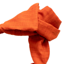 Close up image of luxury, handmade, wide-style headband, in carrot- orange Khadi, tied into a rosette shape. Khadi, sourced on a recent trip to India, is hand spun and handwoven, making each piece uniquely varied in color and texture. Sunrise orange is a classic summery color that will go from the office to the beach with ease.
