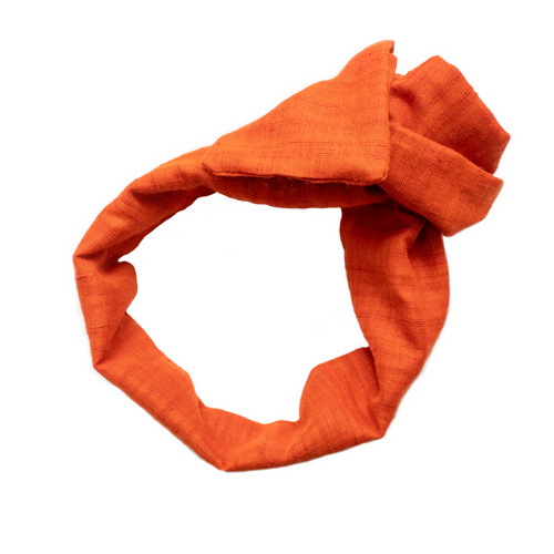Overview of a deep apricot, wire-framed, scarf style headband tied into a rosette, on a white background. Wire framing allows you to sculpt or shape headband into any shape you can think of, including: trendy turban style, wide and flat like Brigitte Bardot, or different types of bows. Flexible shaping of the headband allows for unique,