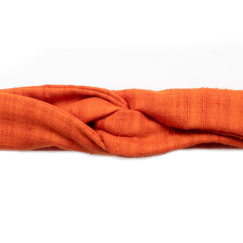 Close up image of luxury, handmade, skinny-style headband, in bright, tangerine orange Khadi, tied into a turban shape. Khadi, sourced on a recent trip to India, is hand spun and handwoven, making each piece uniquely varied in color and texture. Sunrise orange is a classic summery color that will go from the office to the beach with ease.