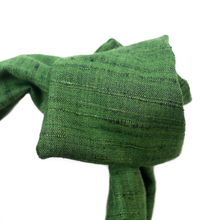 Close up image of luxury, handmade, wide-style headband, in true emerald green Khadi, tied into a rosette shape. Khadi, sourced on a recent trip to India, is hand spun and handwoven, making each piece uniquely varied in color and texture. Deep kelly green is a classic summery color that will go from the office to the beach with ease.