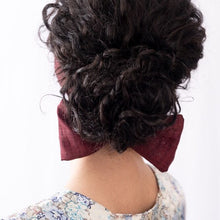 "Picture of the back of a woman, with her hair styled in a bun, wearing ""Maqui"" Maxi as a wide flat headband with the ends styled into a bow below the bun.  Premium, luxury headbands. Purple, eggplant, aubergine, brick, berry, maroon, wine colored cotton khadi."