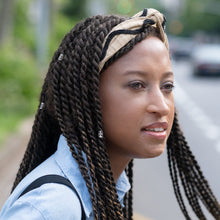 Beautiful woman with braids wears beige wire headband with black beaded detail.