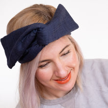 Woman smiles and wears navy wire head wrap