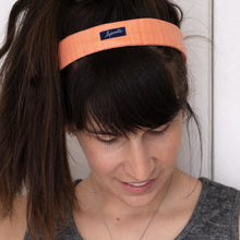 Woman wears pale coral headband and the Lysande label shows.