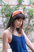 Millenial woman with medium length brown hair and bangs, wearing peach turban style headband and blue draped tank top.