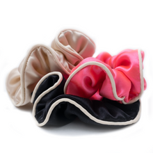 Trio of large silk scrunchies with white piping in beige, pink, and black.