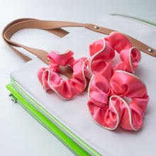 Three coral pink silk scrunchies with white piping laying on top of a white and lime patent bag.