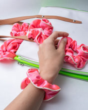 Five coral silk scrunchies with white piping: four laying on top of a white and lime patent bag, one worn on model's wrist.