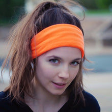 Front view of a dark haired woman with a pony tail wearing an orange fleece ear warmer with tapered ends twisted behind her head.