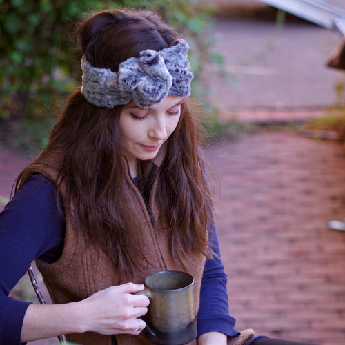 Overview of woman with long dark wavy hair wearing a gray faux fur ear warmer formed into a rose/knot style and holding a mug of coffee.