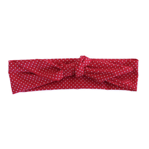 Overview of a red wire-framed bandana with white polka dots tied in a bow.