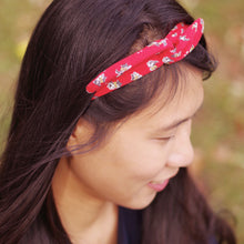 Side view of dark haired woman wearing a red cotton headband that has a small cat pattern.