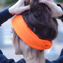 Back view of a dark haired woman holding her hair up to show the tapered ends of an orange fleece ear warmer twisted and tucked behind her head.
