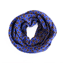 Overview of wire-framed headscarf coiled into a circle. Fabric is bright blue with small black, orange, and white squares.