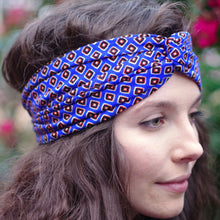 Side view of woman with her brown wavy hair down while wearing a blue headscarf with small black and orange diamonds.
