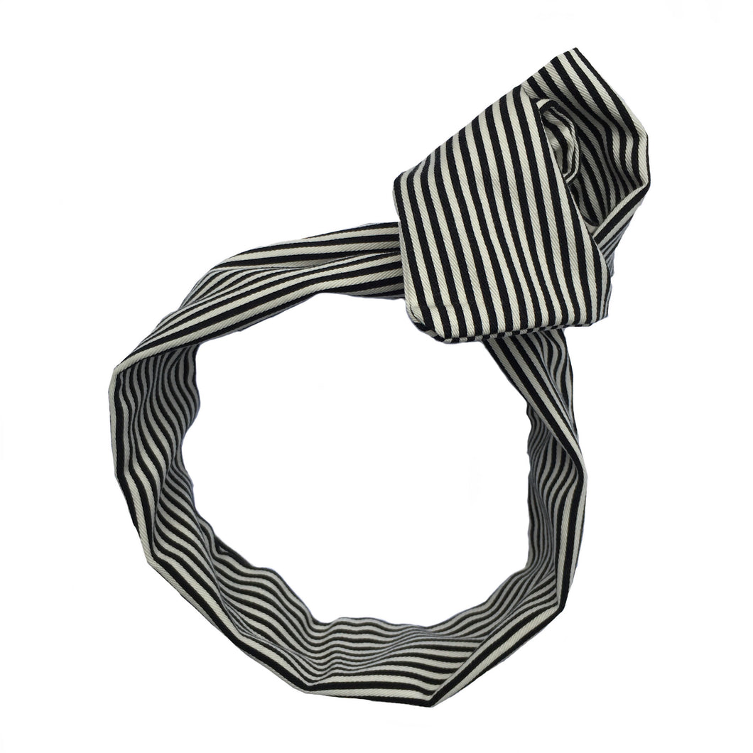 Overview of a wide, white/ cream and black striped cotton twill headband, with the ends twisted into a rose at the crown on a white background. Stylish headache free head wrap. 35 inches long by 4 inches wide wired hair scarf. 50s and 60s, classic, rockabilly, pinup style, adjustable bandanna. Painless hair accessories. Bohemian, vintage, classic, old hollywood head wrap. Sculptural, adjustable hair accessories. Summery, beachy, fall pattern, minimalist hair accessory.