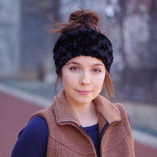 Front view of woman with dark hair in a bun and a camel colored vest wearing a black faux fur ear warmer.