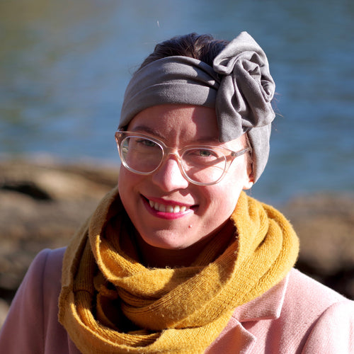 Light haired woman with glasses and mustard scarf wearing a gray faux suede headwrap formed into a rose/knot style.