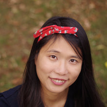 Overview of dark haired woman wearing a red cotton headband that has a small cat pattern.