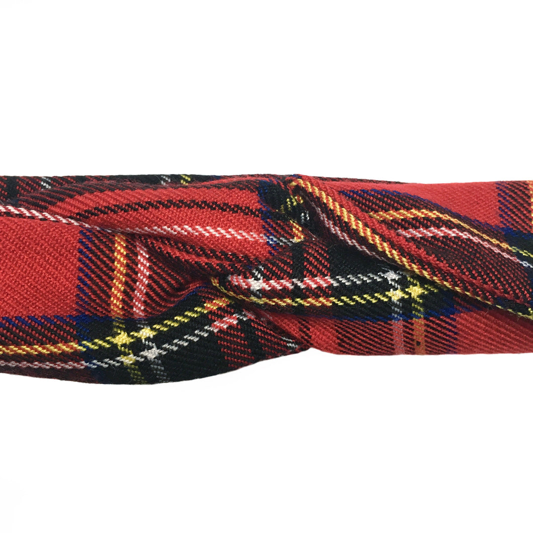 Close up of a red plaid headband with black, blue, yellow, and white plaid pattern on a white background. Skinny, wire-framed headband with ends folded into turban style knot. Headache free hair accessories. Classic, grunge, rock, rockabilly, bohemian, natural, preppy, school uniform, 50's, 60's, 70's, 80's, 90's style hair accessories.