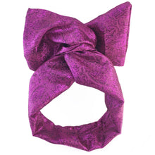Front view of a sparkly magenta headwrap formed into a bow style against a white background.