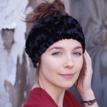 Side view of woman with dark hair in a bun and red sweater wearing a black faux fur ear warmer.