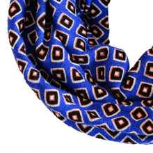 Closeup overview of blue wire-framed headscarf with small black and orange diamonds.