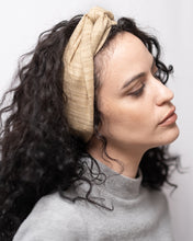 "Image of profile view of woman with dark curly hair wearing the ""jute"" maxi wire-framed headband in a turban style.  Festival, summery hair, beachy hair, wedding guest, shower, brunch, office, pool party, resort, vacation, evening wear, date night, fourth of july, memorial day, labor day, easter, birthday, kentucky derby, red carpet, christmas, thanksgiving, new year's eve."