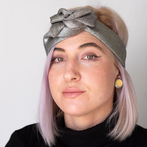 Image of woman with blonde and purple hair wearing metallic silver fabric wire-framed headband tied into a fancy bow. Special Occasion headband.