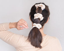 "back view of brunette woman with fancy tiered ponytail wearing three large ""jute"" beige silk scrunchies with white piping."