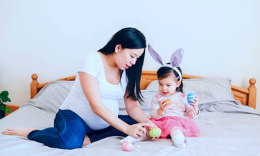 Easter activities for toddlers - pregnant mum and toddler playing with Easter eggs on a bed