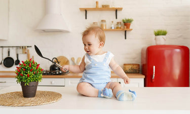 Food inspired baby names - baby boy sitting on kitchen counter holding spoon
