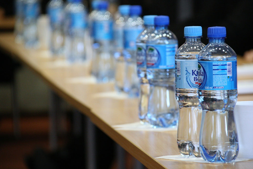 Long row of plastic water bottles on wooden table