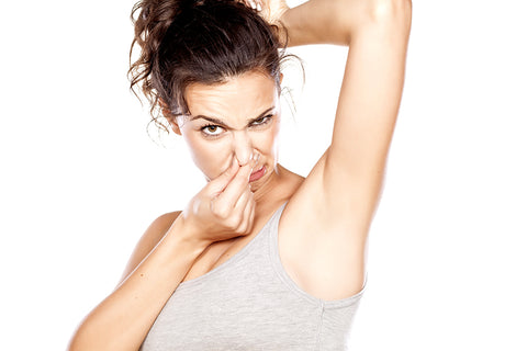 Woman covering her nose from the smell of her armpits as she raises her arm
