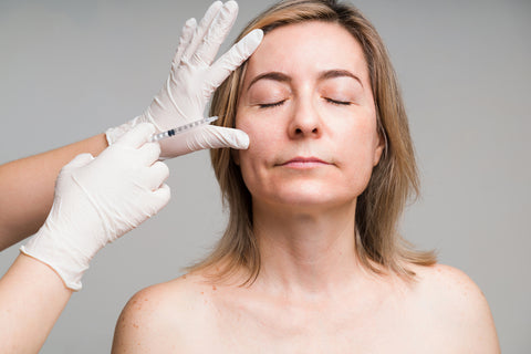 Medical esthetician performing service on woman's face