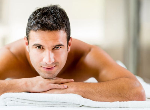 smiling man facedown on waxing table