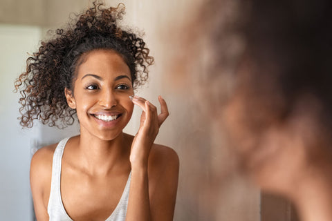 Woman smiling doing her facial skincare routine