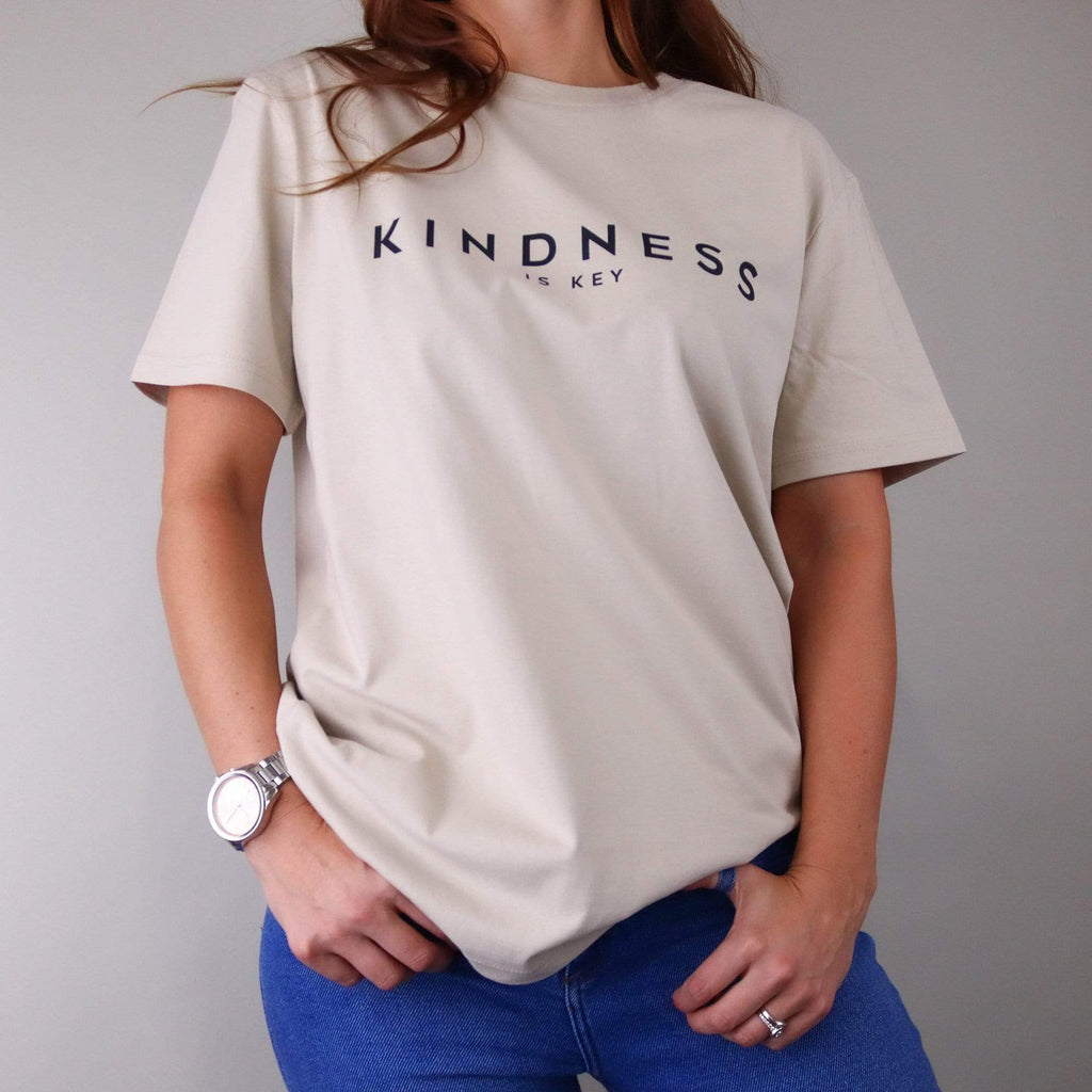 Woman wearing a nude t shirt with text that reads 'kindness is key' in black by Original Monkey Gifts. Woman also wears blue denim jeans, silver watch and white gold engagement and wedding rings.