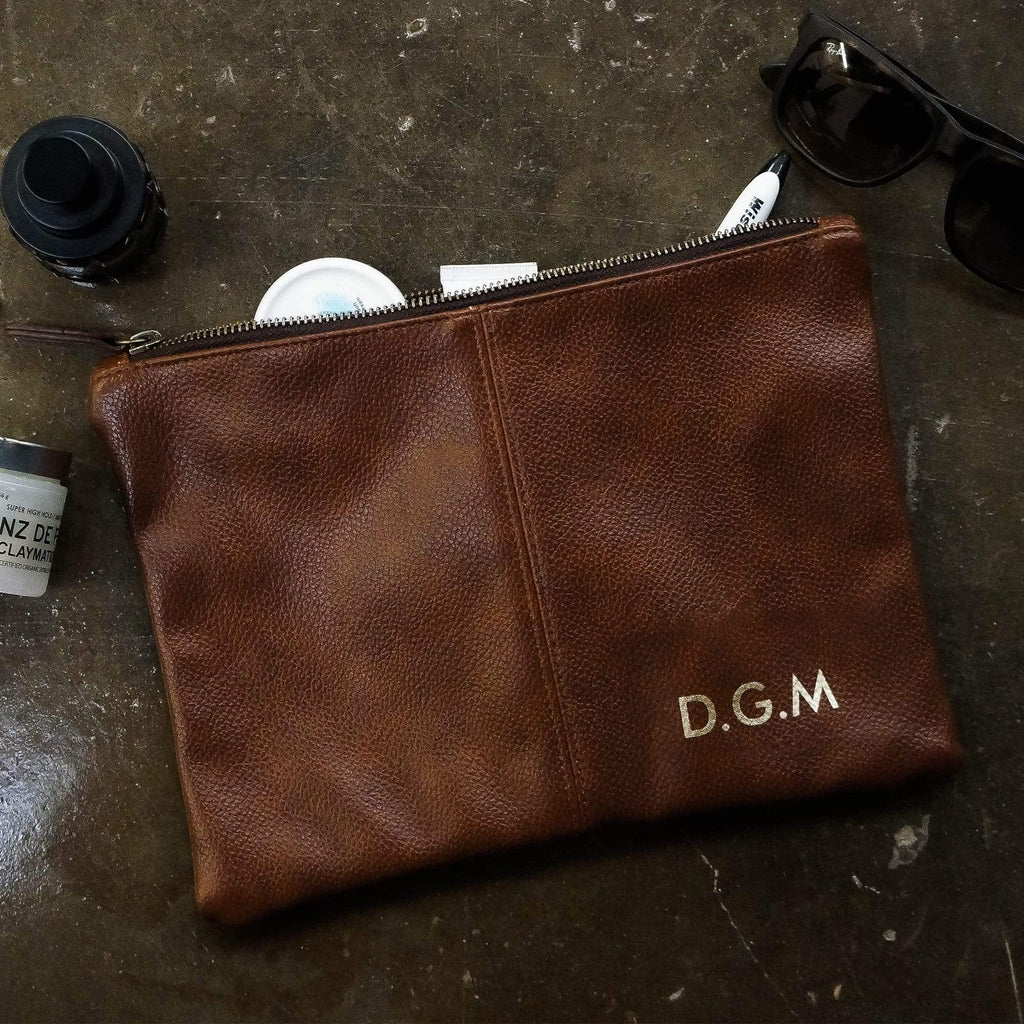 Brown leather toiletries bag with personalised initials in gold by Original Monkey Gifts. Concrete worktop with toothbrush and mens hair products.
