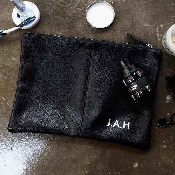 Black leather toiletries bag with personalised initials in silver by Original Monkey Gifts. Concrete worktop with toothbrush and mens hair products.