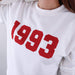 Woman wearing white hoodie with personalised year of 1993 in red text by Original Monkey