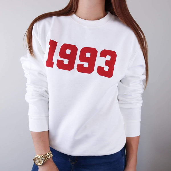 Woman wearing white hoodie with personalised year of 1993 in Red text also wearing blue jeans and gold watch. By Original Monkey Gifts.